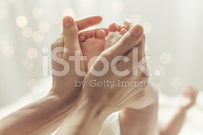 stock-photo-76939559-mother-touching-feet-of-newborn